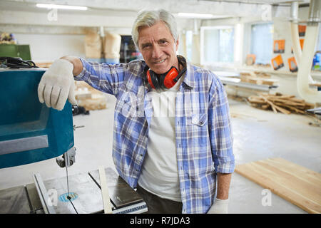 Smiling carpenter leaning on drilling machine - Stock Photo