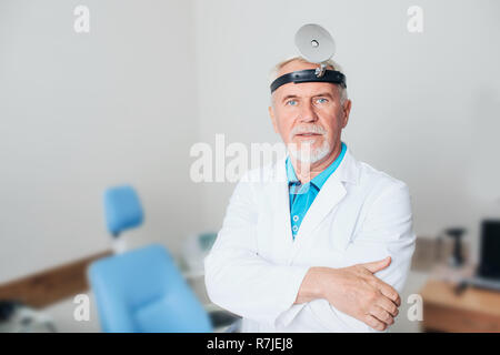 Portrait of senior ENT doctor at medical office - Stock Photo