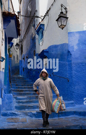 Morocco, Chefchaouen, Medina, Arab man wearing Djellaba walking down narrow street of blue painted hillside houses - Stock Photo