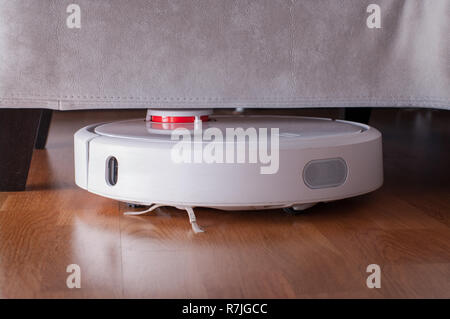Robotic vacuum cleaner runs under sofa in room on laminate floor. Robot controlled by voice commands to direct cleaning. Modern smart cleaning technol - Stock Photo