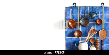 Kitchen interior with vintage copper utensils. old style cookware kitchenware set. Pots, kitchen spoon, skimmer hanging on blue tile wall. Copy space, white background - Stock Photo