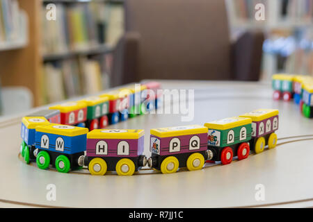 This colorful train with numbers and letters of the alphabet painted all over are magnetically connected in the playroom. - Stock Photo