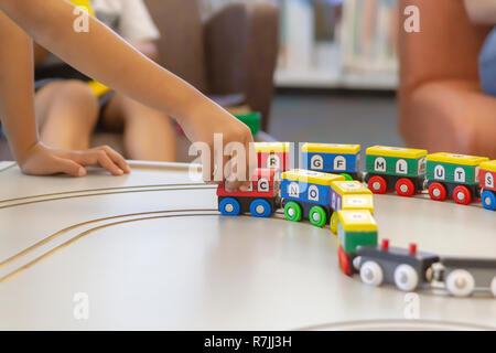 A child's​ hand pulls the train along. The colorful train with letters of the alphabet and numbers painted all around are magnetically connected. - Stock Photo