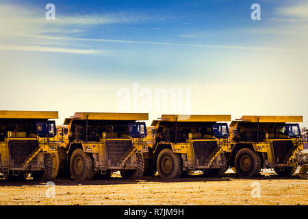 Four yellow dump trucks in mine put in row, with blue sky background and clouds - Stock Photo