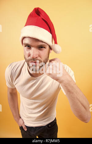 Man in santa hat with fist hand on orange background. Power, strength concept. Christmas and new year party. Winter holidays celebration. - Stock Photo