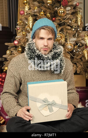 Winter holidays preparation, celebration. Man with gift box sit at Christmas tree. Boxing day concept. New year, xmas, eve, party. Macho with serious face in hat, sweater hold wrapped present. - Stock Photo