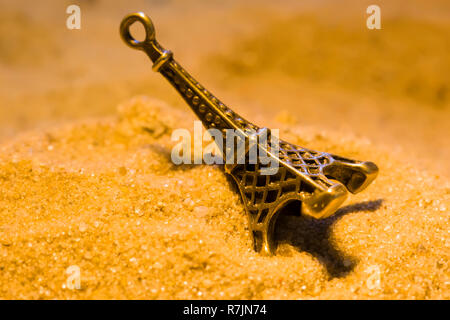 Toy Eiffel Tower in the yellow sand close-up - Stock Photo