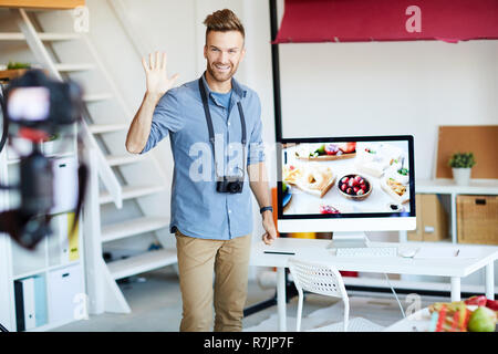 Portrait of handsome young man waving at camera while leading online training session on food photography, copy space - Stock Photo