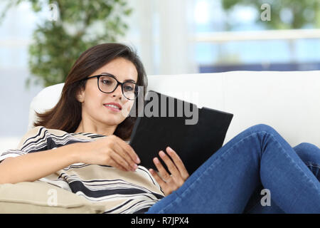 Happy woman reading an ebook sitting on a couch in the living room at home - Stock Photo