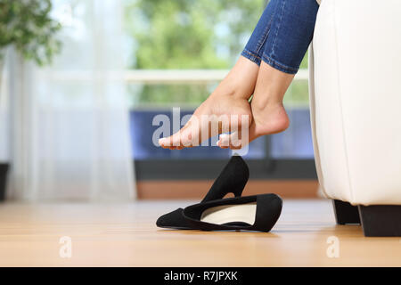 Close up of a beautiful woman legs and shoes resting sitting on a couch in the living room at home - Stock Photo