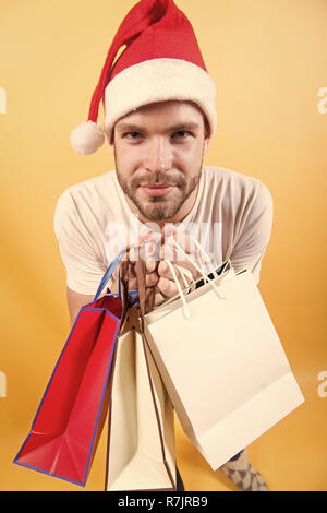 Black friday sale concept. Man shopper in santa hat with paperbags. New year, xmas presents. Macho hold shopping bags on orange background. Winter holidays celebration.