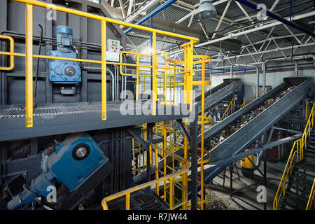 Refiner and chain-stepped conveyor equipment of modern waste recycling plant transports waste from receiving department to sorting, recycling and disp - Stock Photo