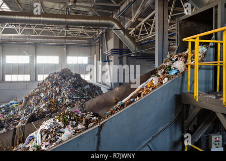 Refiner and chain stepped conveyor equipment of modern waste recycling plant transports waste from receiving department to sorting, recycling and disp - Stock Photo
