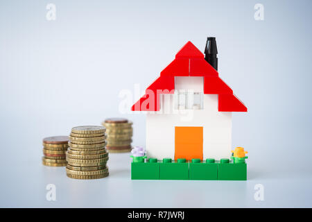 Stacks of coins and simple house made of toy building bricks, on gray background. Concept photo of mortgage, real estate business or house ownership. - Stock Photo