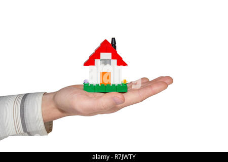 Man holding a simple house made of toy building bricks on his palm. Isolated on white. Concept photo of real estate business or house ownership. - Stock Photo
