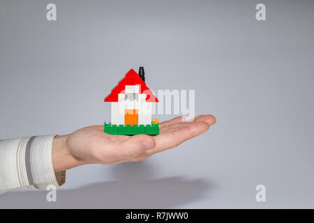 Man holding a small house made of toy building bricks on his palm. Gray background. Concept photo of real estate business or house ownership. - Stock Photo