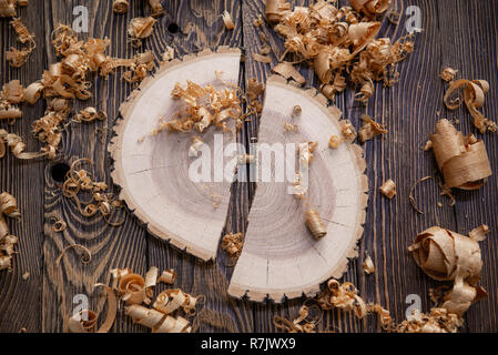 Wood shavings and Ashen tree cross section on the carpenter's workbench close up: woodworking and carpentry concept - Stock Photo