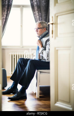 Mature businessman on a business trip in a hotel room, getting dressed. - Stock Photo