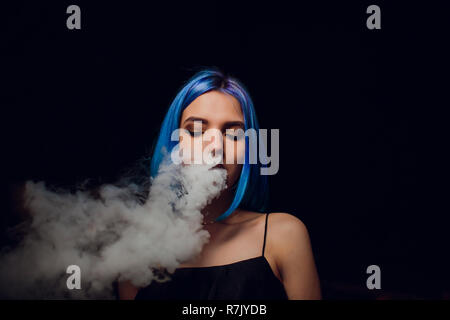 young woman smoking electronic cigarette against a black background - Stock Photo