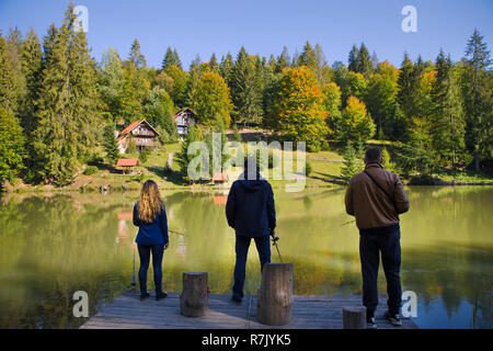 fishing friends on the lake in a beautiful autumn forest. - Stock Photo