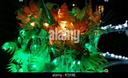 Close up picture of an orange flower made with fairy christmas lights shining at night in a garden - Stock Photo