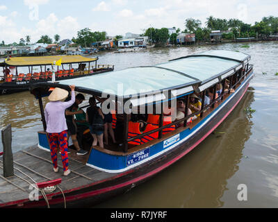 Tourists boarding cruise boat at boat dock at Mekong riverside village Cai Be for a trip along this iconic river to floating market Vietnam  Asia - Stock Photo