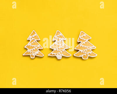 Christmas gingerbreads Flat lay photo Classic Christmas cookies in shapes of fir tree on bright yellow background Template for posters - Stock Photo