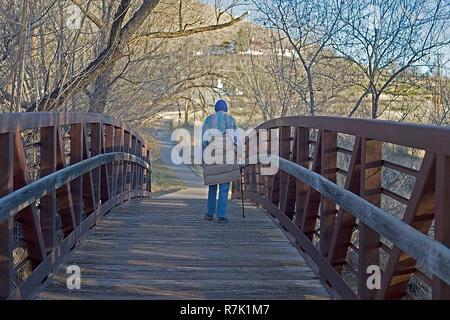 Elderly woman walking in a public park. - Stock Photo