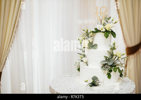 White wedding cake with flowers.  The word Love with heart. - Stock Photo