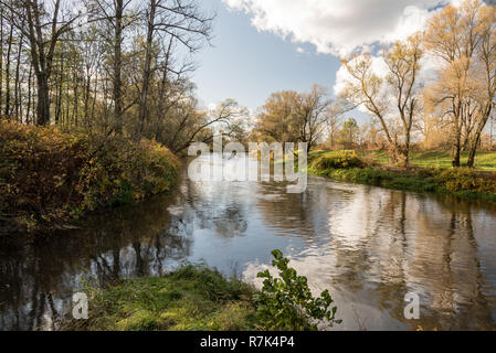 Stonavka and Olse river tributary in Karvina city in Czech republic with colorful trees around during autumn day with blue sky and clouds - Stock Photo