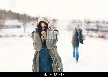 Snowball fight. Winter couple having fun playing in snow outdoors. Young joyful happy young man and woman. - Stock Photo