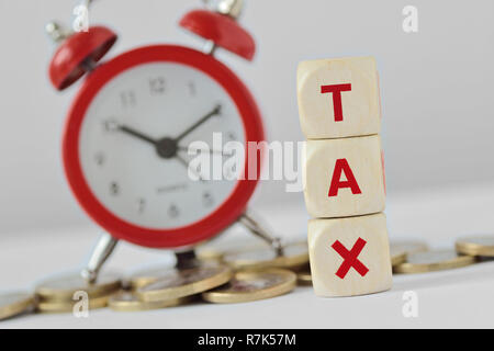 The word Tax written with wooden blocks and alarm clock on coins in the bakground - Tax time concept - Stock Photo