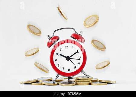 Alarm clock with falling coins on white background - Time is money concept - Stock Photo