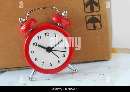 Alarm clock and card box on calendar - Delivery time concept - Stock Photo