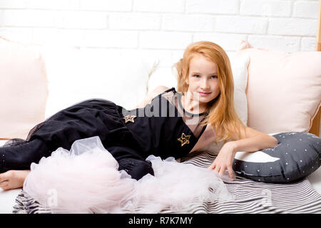 good looking girl looking at the camera while lying on the bed - Stock Photo