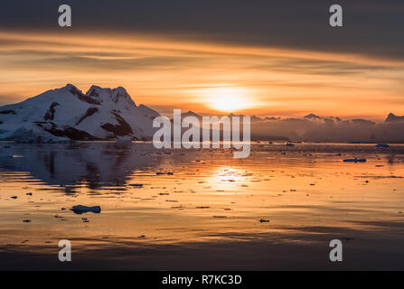 Sunset over antarctic lagoon with drifting icebergs and snow peaks in the background, Lemaire Channel, Antarctica - Stock Photo