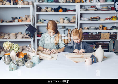 two clever kids modeling in clay