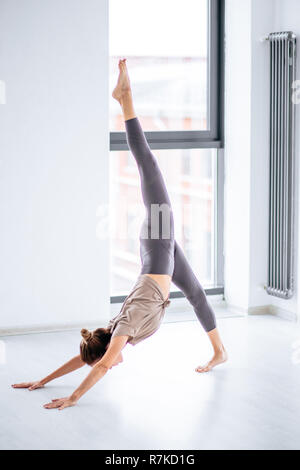Sportive slim young woman doing complicated aerobic yoga exercises indoors - Stock Photo