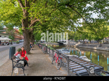 Two young women sitting on the banks of the River Aura (Aurajoki) in the historic centre, Turku, Finland - Stock Photo