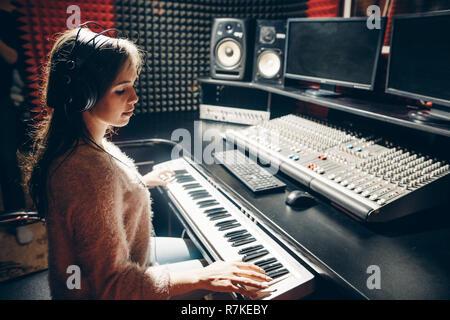 close up side view photo. talented beautiful girl plaing on the synthesizer - Stock Photo