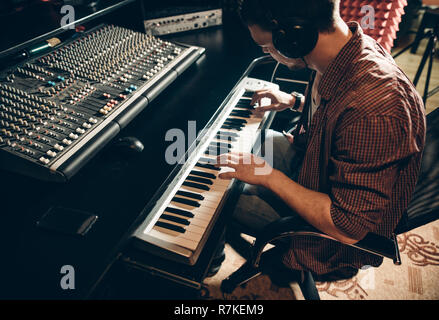 man in headphones playing on the synthesixer - Stock Photo