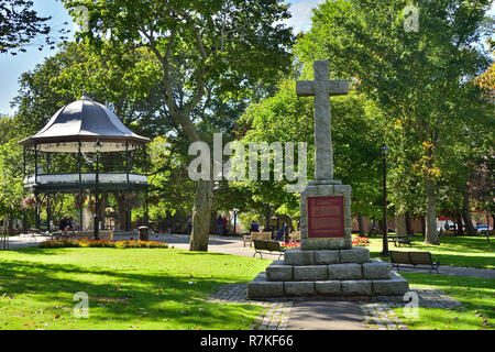 In King Square a stone memorial cross to honor the landing of the first settlers, the loyalist in the city of Saint John New Brunswick Canada. - Stock Photo