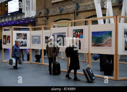 London, UK. 10th December 2018. Passengers view a photography exhibition at London's Kings Cross Station in London, Britain, Dec. 10, 2018. A photography exhibition celebrating the 40th anniversary of China's reform and opening-up is launched on Monday at London's Kings Cross Station. The exhibition titled Reform and Dreams, commissioned by the China International Culture & Image Communication Corporation, features 80 stunning photographs taken over the last 40 years by photographers with Xinhua News Agency. Credit: Han Yan/Xinhua/Alamy Live News Stock Photo