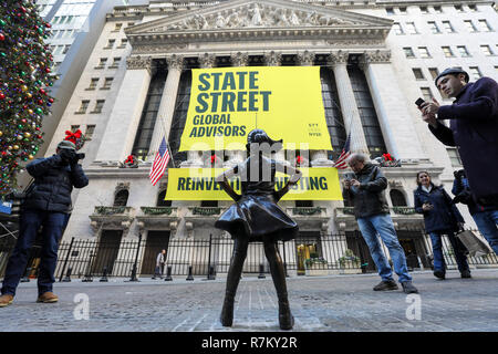New York, USA. 10th Dec 2018. 'Fearless Girl' is seen on the street in front of the New York Stock Exchange in New York, the United States, Dec. 10, 2018. 'Fearless Girl,' a celebrated bronze statue located in New York City's Financial District, was unveiled at her new home in front of the New York Stock Exchange (NYSE) Monday morning. 'Fearless Girl' was initially installed face to face with the iconic 'Charging Bull' statue at the Bowling Green Park in Lower Manhattan. Credit: Xinhua/Alamy Live News Stock Photo