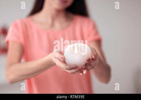 close up.beautiful young woman with a burning candle - Stock Photo