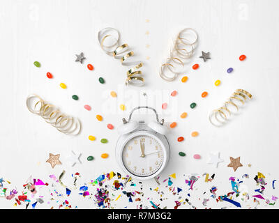 alarm clock on white background with different colorful new year items - Stock Photo
