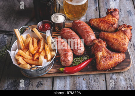 Grilled chicken wings,sausages french fries, white and red sauce on a wooden surface. - Stock Photo