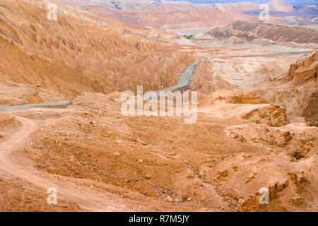Road in the Atacama desert between salt formations at Valle de la Luna, spanish for Moon Valley, also know as Cordillera de la Sal, spanish for Salt M - Stock Photo