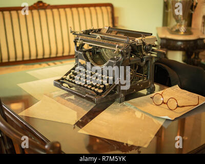 Vintage desk with the old typewriter and oldstyle round glasses on it - Stock Photo
