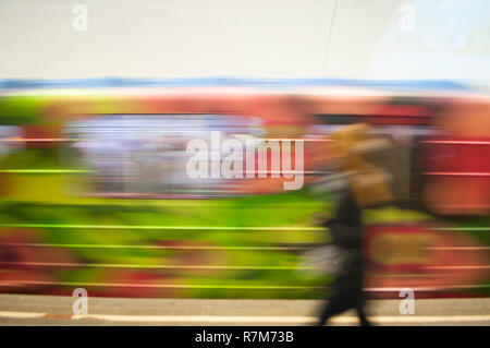 Blurred motion of the colorful train with living coral color elements in an underground station. - Stock Photo
